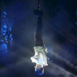 Illusionist hangs upside down over water in straight jacket