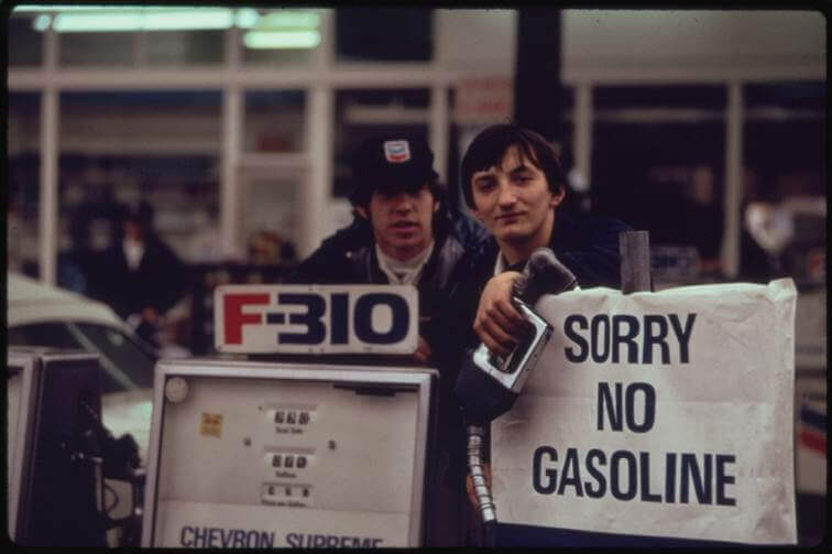 "Gas station attendant peers over ""out of gas"" sign in 1973"