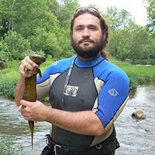 Dr. Shem Unger holds a giant salamander.