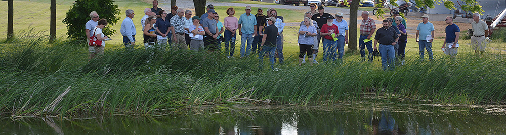 Pond management workshop with crowd by pond.