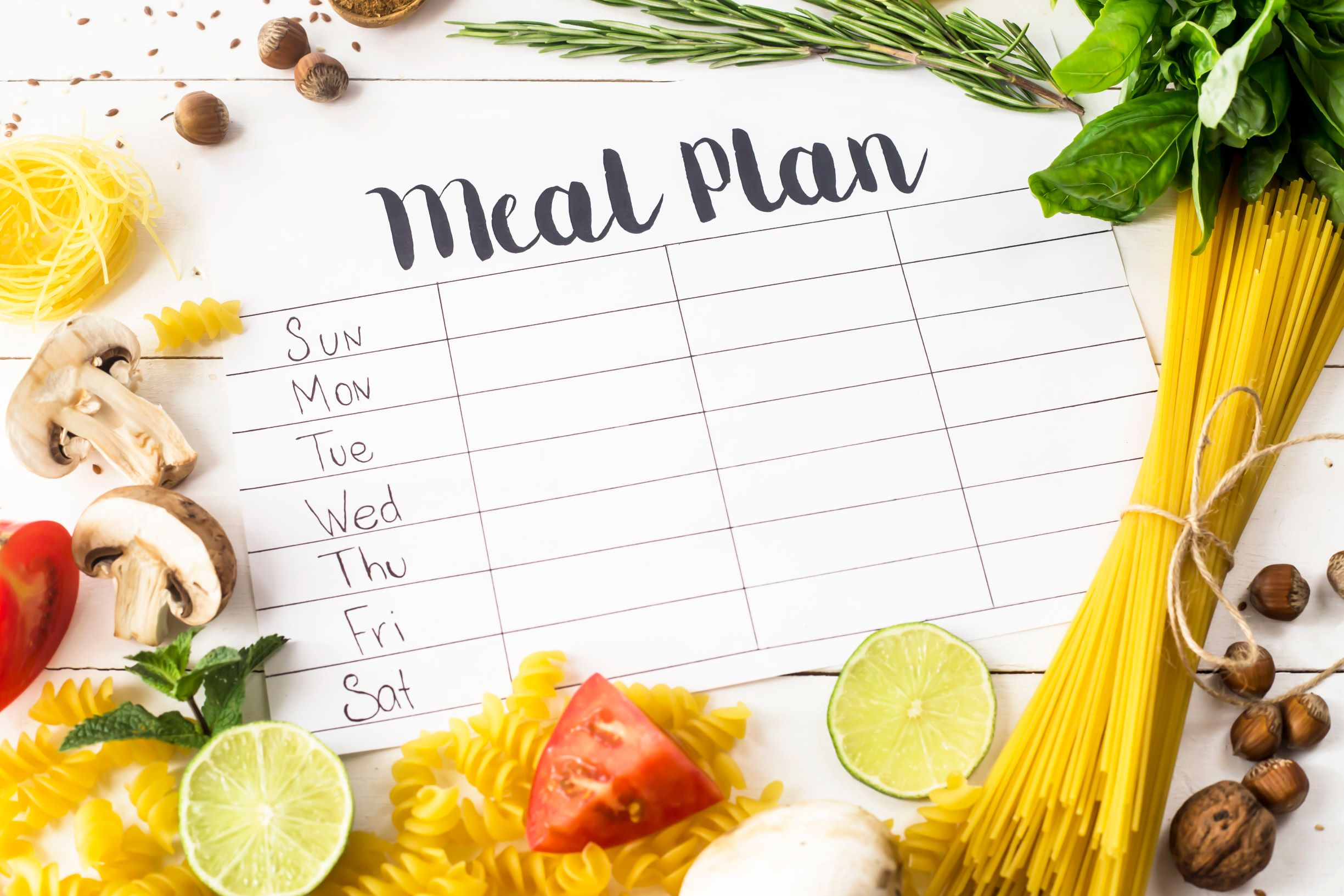 Meal plan weekly calendar with veggies surrounding it.