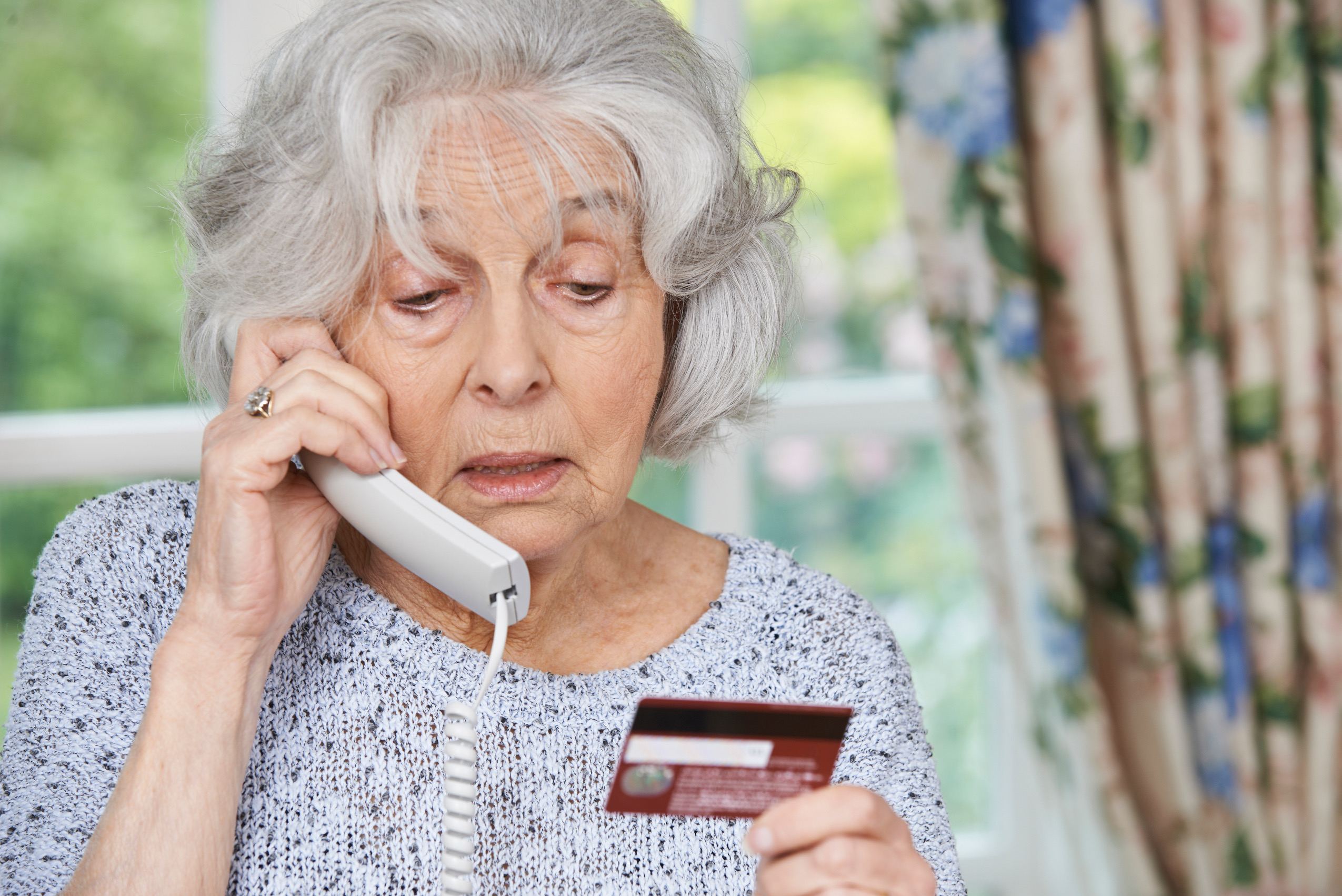 Senior woman giving credit card information over the phone.