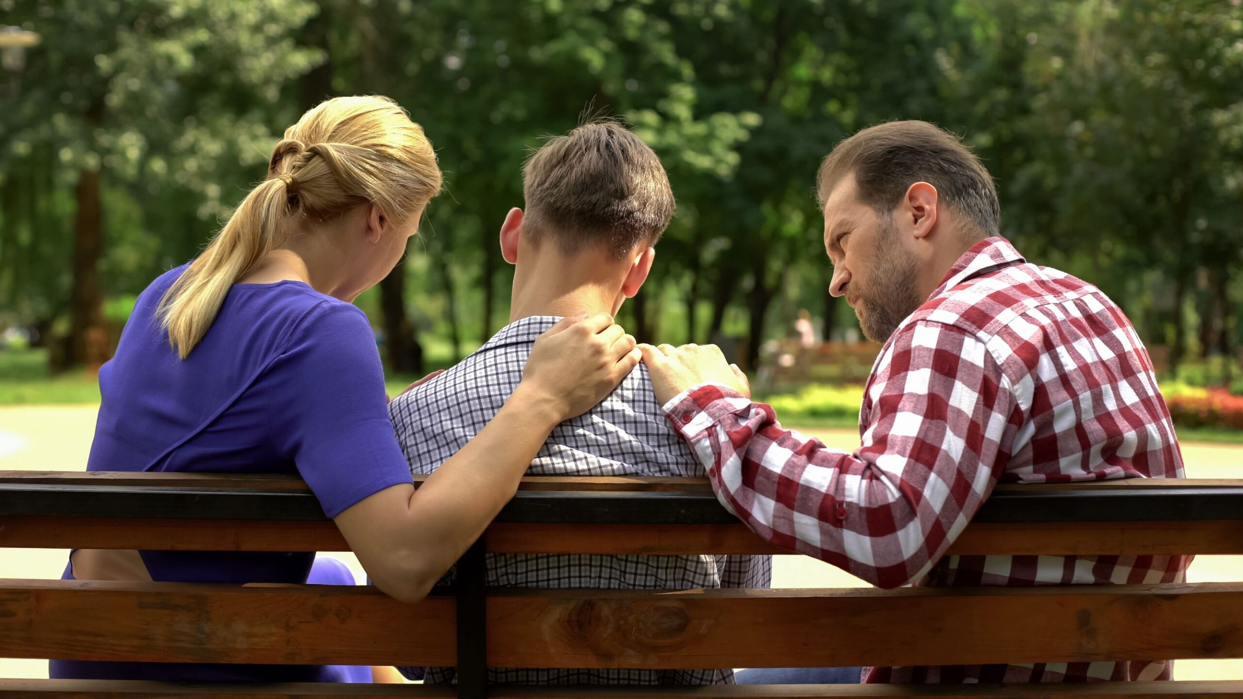 Parents sitting with son on an outdoor bench talking