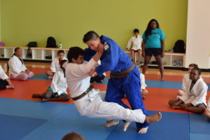 Judo instructors demonstrates a standing takedown on a camper.