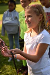 Smiling girl handling snake