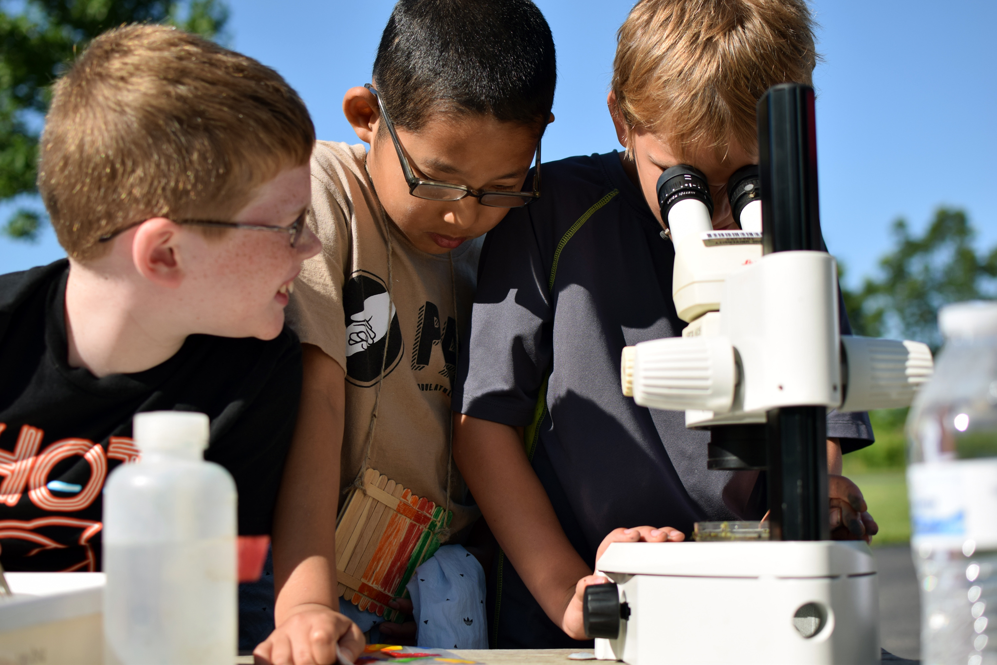 Boys using a microscope for scientific experimentation
