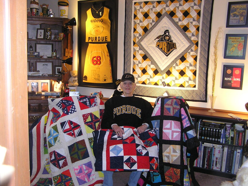 Roger Johnson sits in his home's Purdue room with three of the quilts he made in memory of his wife, Vicki.