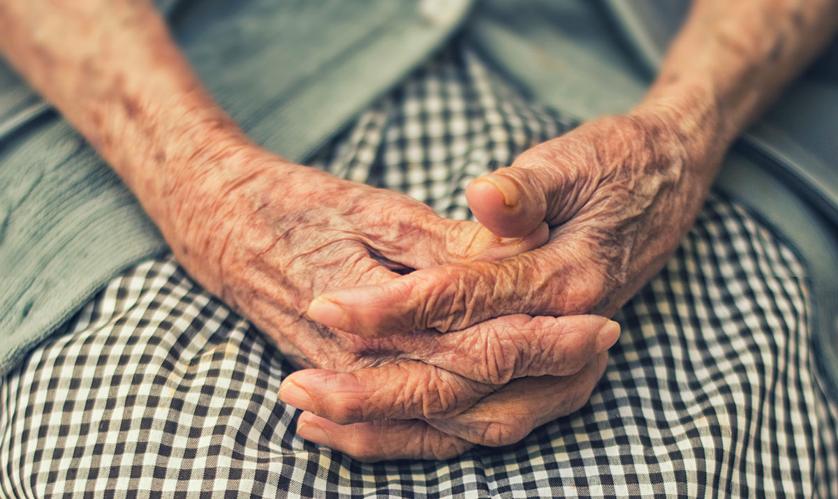 Elderly woman's hands folded in lap