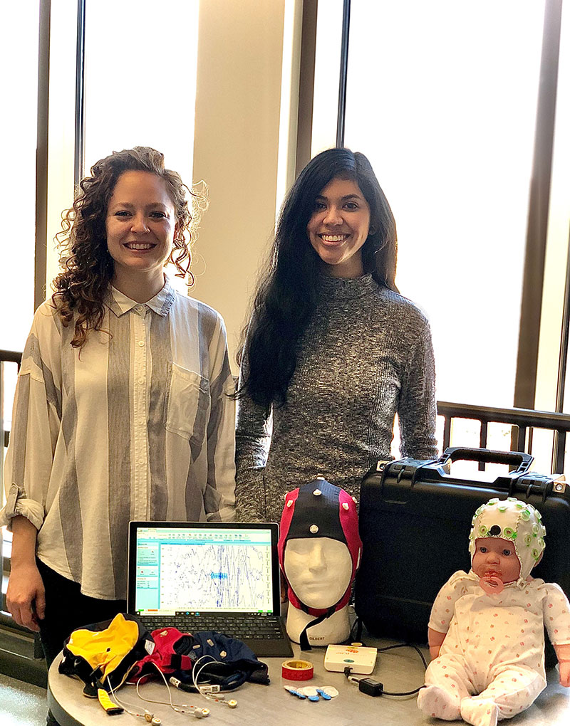Clinical Psychology Ph.D. students Roslyn Harold (left) and Kimberly Galvez-Ortega (right)  stand next to research kits to be sent to families for at-home neurological research studies. The kits will send data to Professor Daniel Foti's team on Purdue University campus.