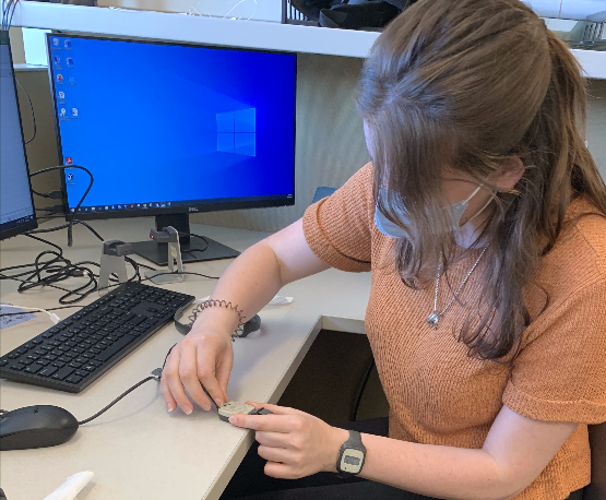 In A.J. Schwichtenberg's lab, students learn to use actigraphy, a small wrist worn device that measure activity which can be converted into rough estimates of sleep and wakefulness. Here a student is wearing an actigraph and is plugging another one in to download the data.