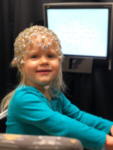 A young participant in Professor Brandon Keehn's ongoing autism research wears electroencephalogram (EEG) equipment.