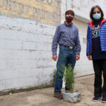 """Sa Liu, right and assistant professor in the School of Health Sciences, stands at """"ground zero"""" of the Martinsville superfund site, which saw a dry-cleaning company illegally dump gallons of PCE into a well in 1991, with Tom Wallace, founder of a Martinsville PCE task force. The groundwater as well as the air inside homes and businesses near the site still contain amounts of the dangerous chemicals 30 years later."""