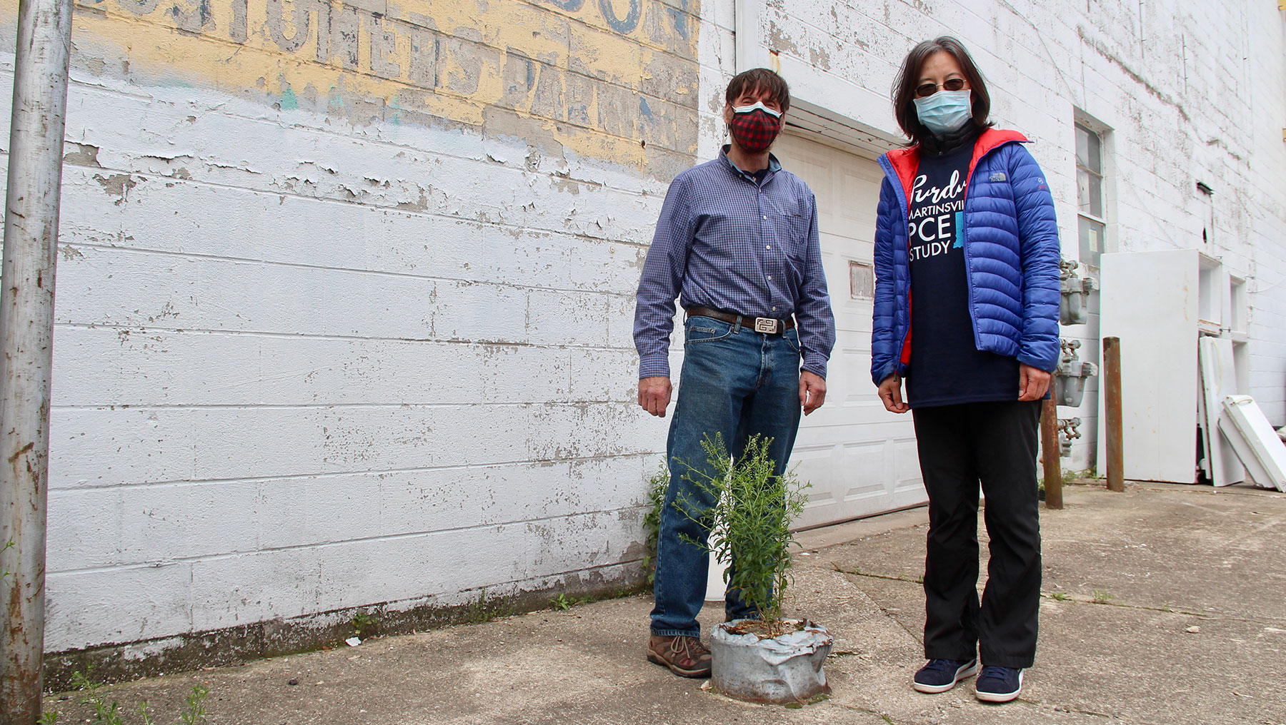 """Sa Liu, right and assistant professor in the School of Health Sciences, stands at """"ground zero"""" of the Martinsville Superfund site, which saw a dry-cleaning company illegally dump gallons of PCE into a well in 1991, with Tom Wallace"""