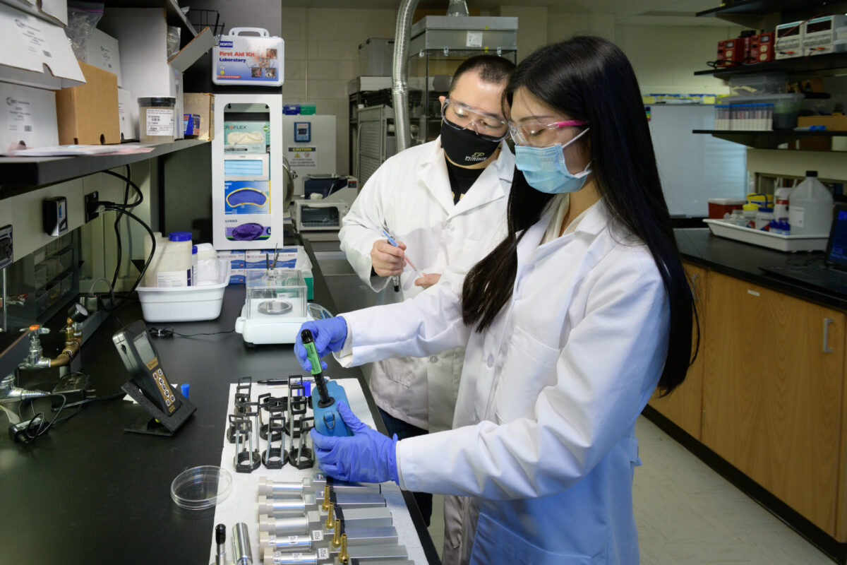 Jae Hong Park, assistant professor of health sciences and left, works with Li Liao, a health sciences PhD student, in creating new bioaerosol detection technology.