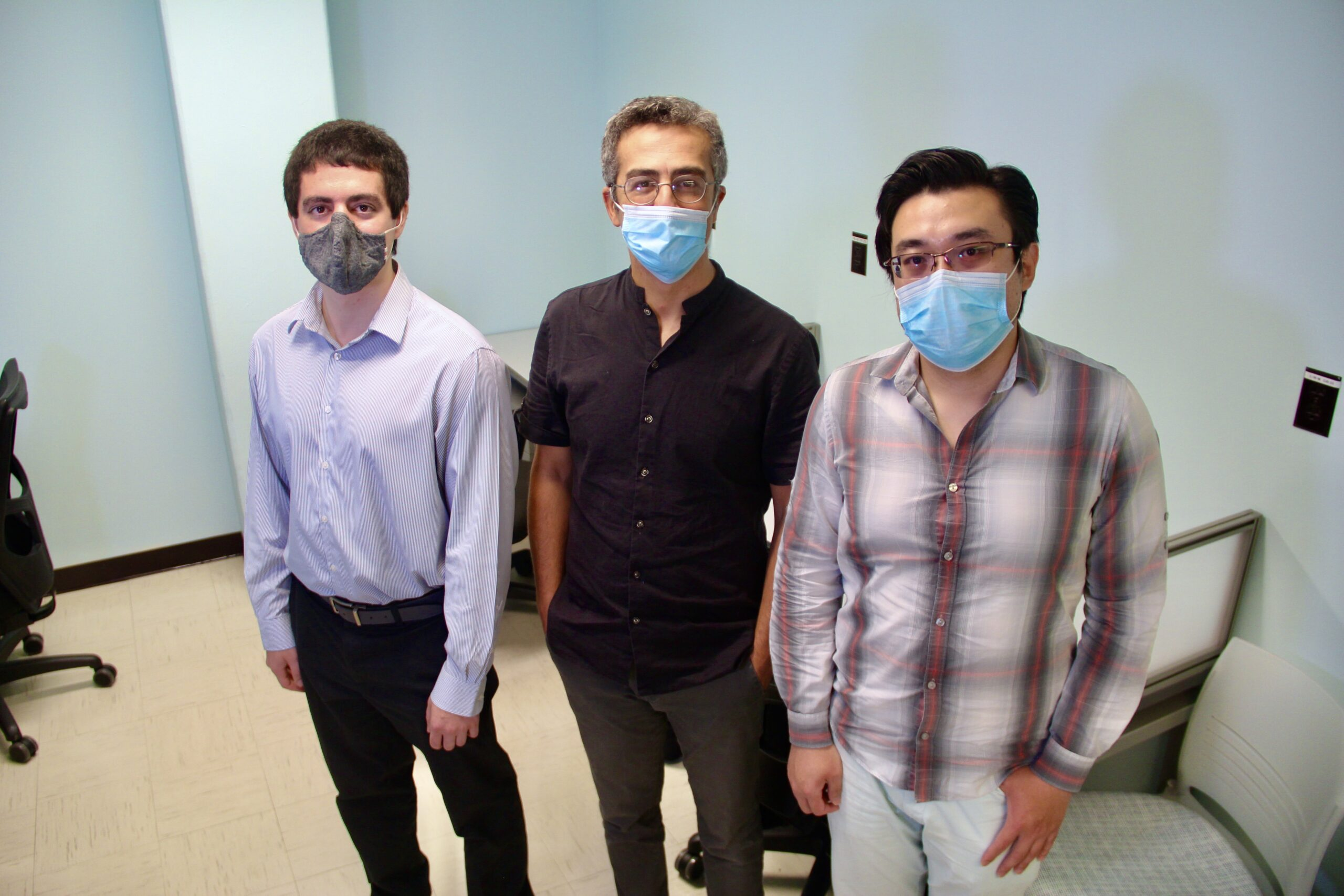 Uzay Emir stands with his doctoral students Xin Shen and Nicholas Farley