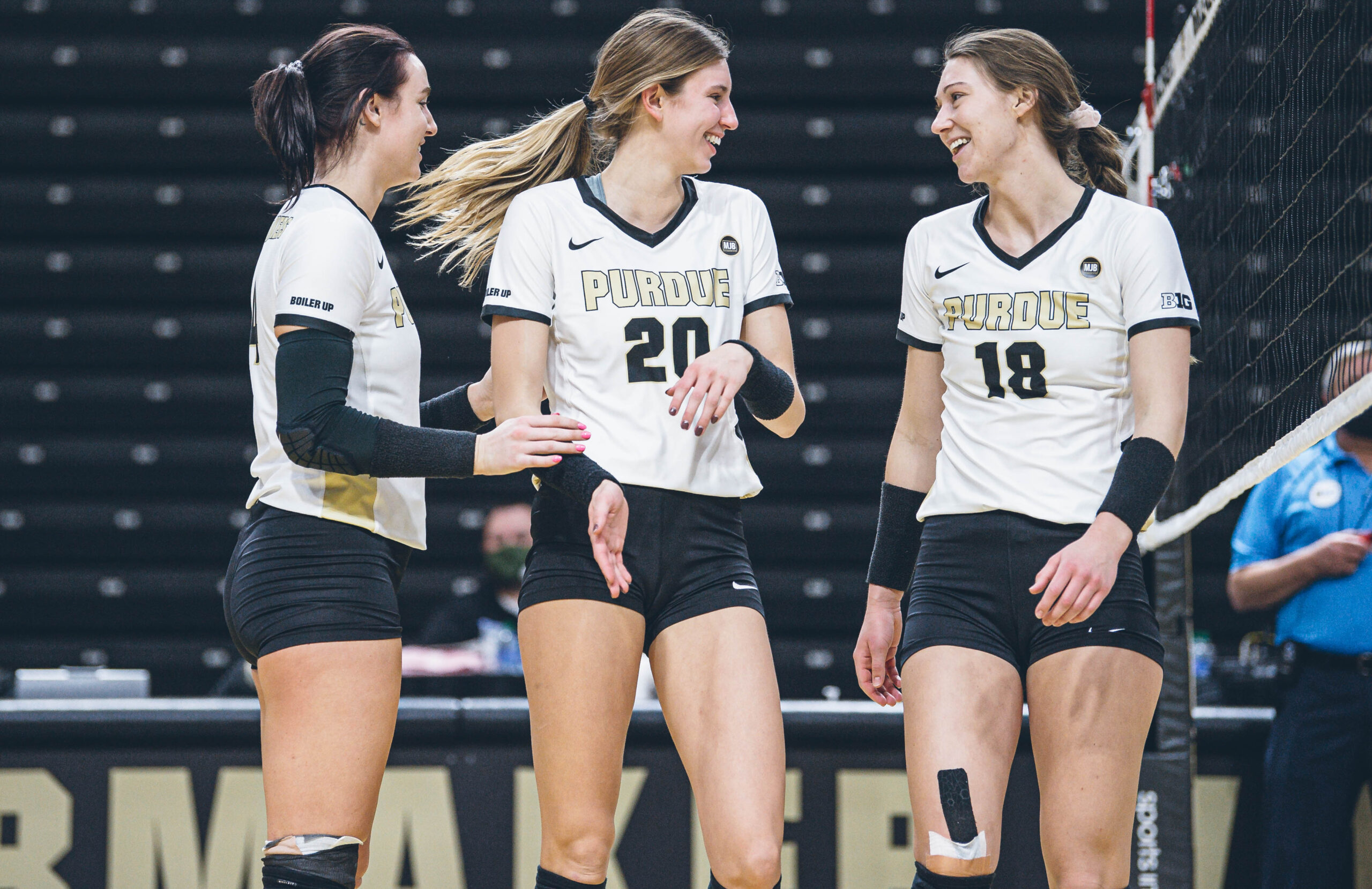 Caitlyn Newton, Grace Cleveland and Jael Johnson, from left, celebrate a point during a Purdue volleyball game.