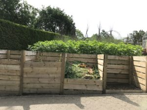 Multiple large wood slat compost bins next to each other