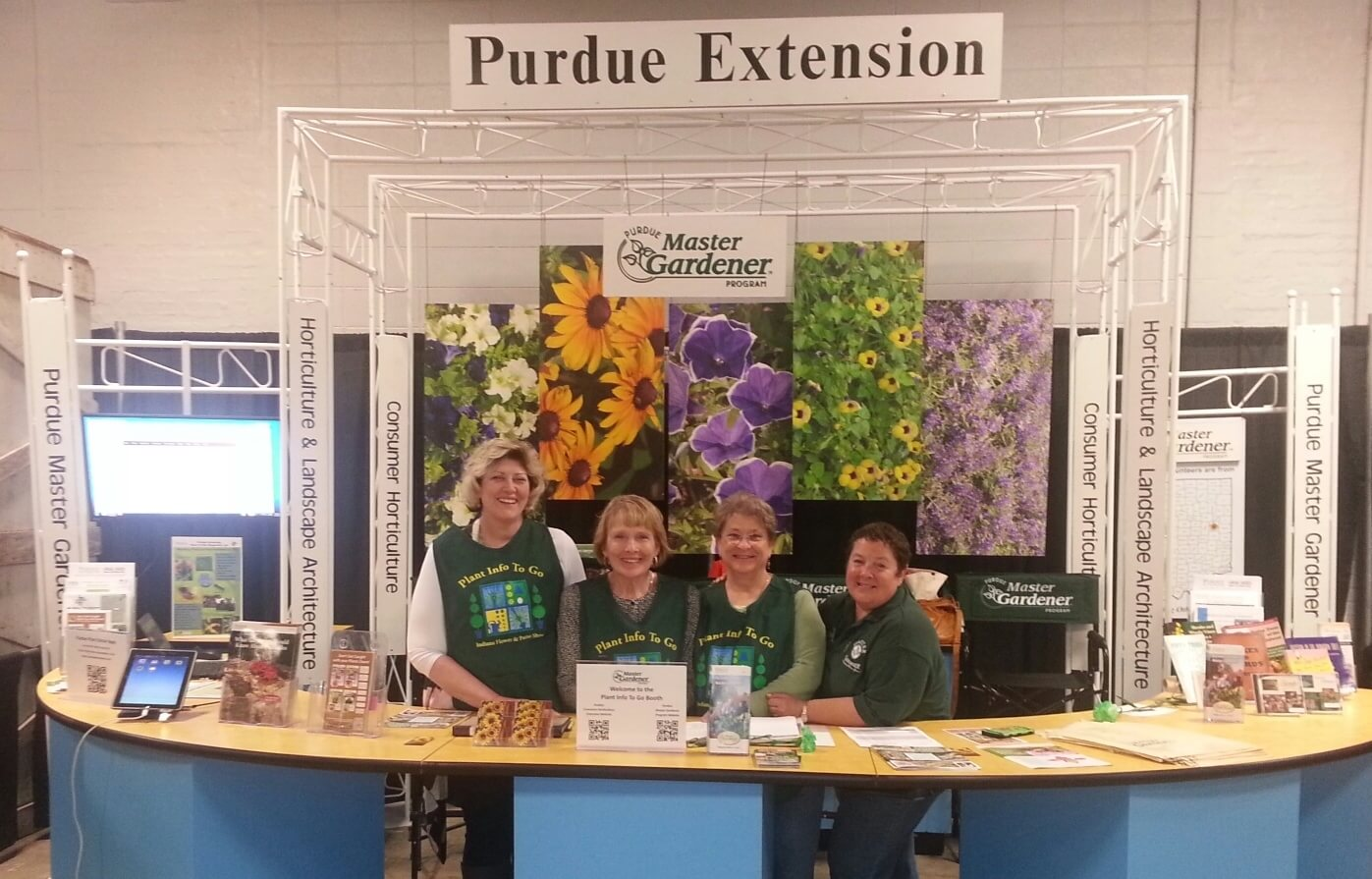 Master Gardener Booth with Large floral pictures hanging at the back of the booth. Curved counter across the front with 4 master gareners standing behind the booth, ready to answer questions. Literature of various kind is sitting on the counter.