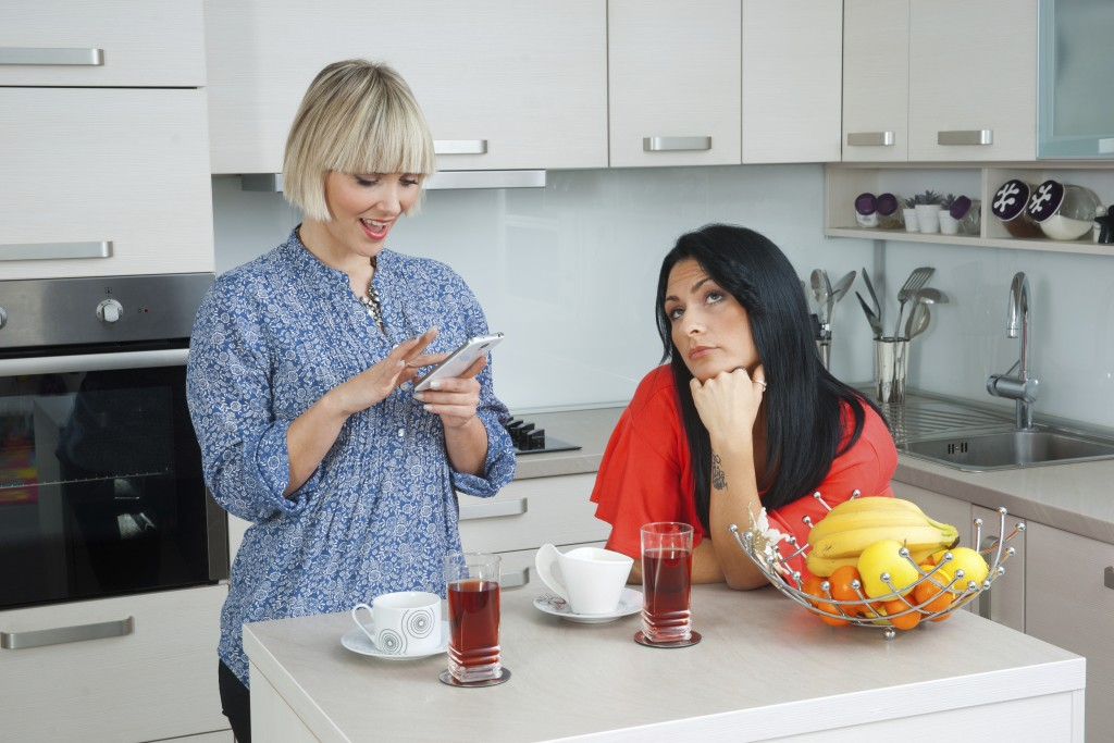 two attractive woman friends in kitchen , one bored other texting on mobile phone