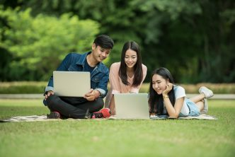 Asian college students studying on lawn