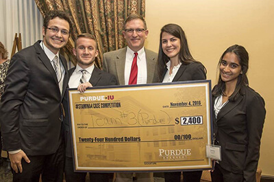 Students and man holding oversized check