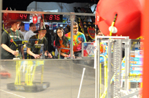 Teams from Hatton, N.D. (left), and Rolling Meadows and Wheeling high schools in suburban Chicago, work together to guide their robots to move inflatable balls during the 2008 FIRST Boilermaker Regional robotics competition at the Purdue Armory. The three-team alliance of the Hatton and Rolling Meadows-Wheeling teams, and another team from Indianapolis, captured first place and qualified for the international competition in Atlanta. Forty teams from six states competed in the regional. (Purdue News Service file photo/David Umberger.)