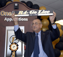 Gary Newsom hold a sign celebrating the fourth and final software release and go-live date of the new Banner system at Purdue University.