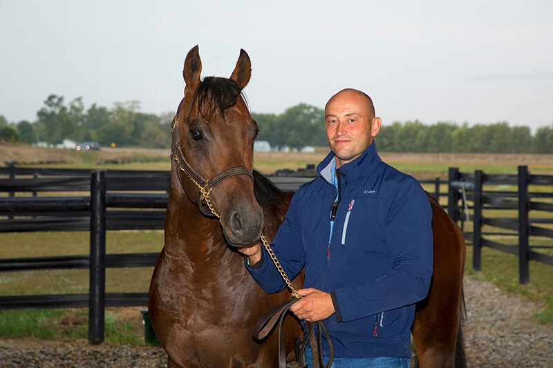 Tim Gudehus standing by a horse