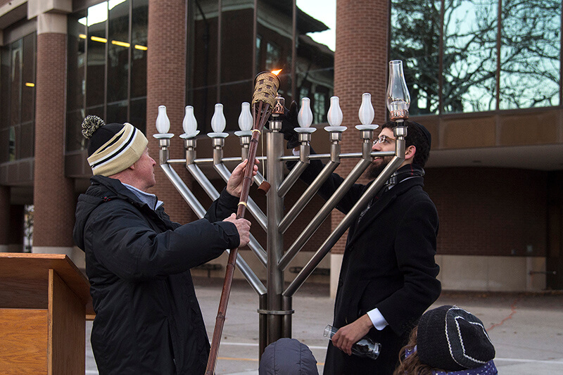 Mitch Daniels lighting menorah with Rabbi Levi Tiechtel