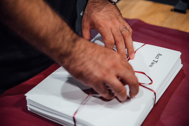 Nassim hands untying ribbon around envelopes