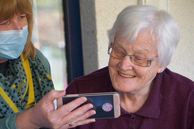older woman looking at smartphone held by woman in mask