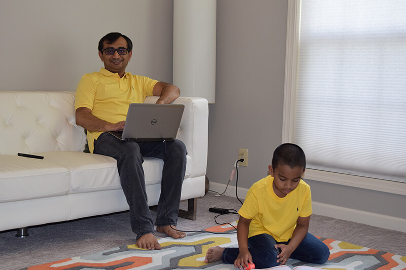 Mohammad Rahman sitting on couch and son playing with toys on floor