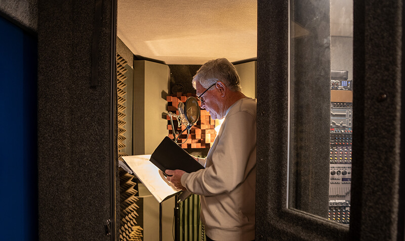 Mike Piggott reads graduates' names in a recording studio