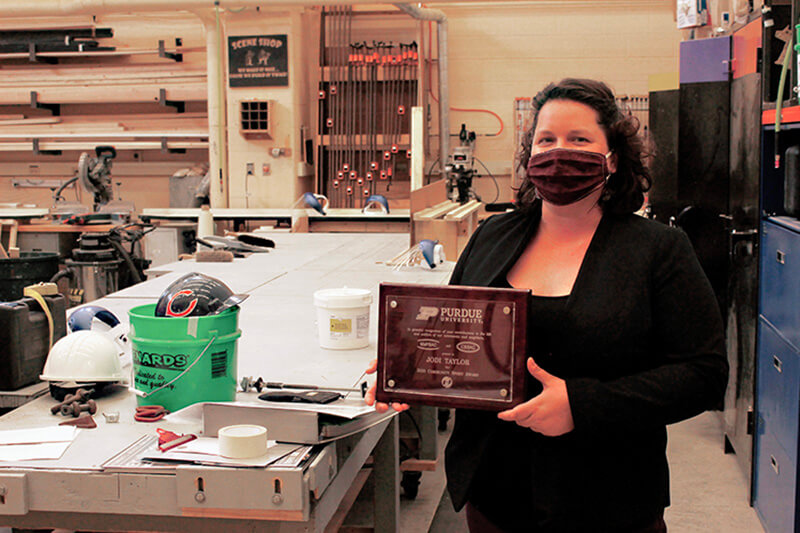 Jodi Taylor with plaque at Purdue Theatre's Scene Shop